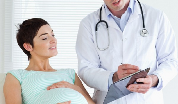 Pregnant woman lying down talking to her doctor in a room